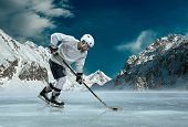 pic of ice hockey goal  - Ice hockey player in action outdoor around mountains - JPG