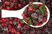 foto of berries  - White porcelain bowl with frozen berries and mint leaves stands in the midst of other berry fruits - JPG