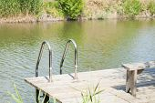 stock photo of dock a pond  - wooden pier with a handrail on the pond - JPG