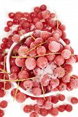 stock photo of ice crystal  - Top view of frozen currants with stems covered with ice crystals in a white porcelain bowl on white background - JPG