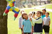 stock photo of pinata  - Children Hitting Pinata At Birthday Party - JPG