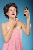 stock photo of hair curlers  - Young woman preparing to party girl styling hair with curlers applying makeup red lipstick retro style blue background - JPG