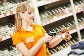 stock photo of cashiers  - seller cashier with bar code scanner scanning plumber valve at store - JPG
