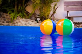 picture of pool ball  - Colorful beach balls floating in pool.