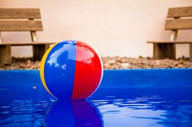 stock photo of pool ball  - Colorful beach ball floating in pool.