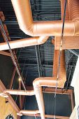 Copper Ducts Under Black Ceiling
