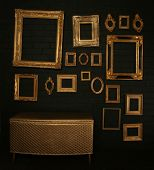Gallery display - vintage gold frames and a chest on a black brick wall