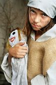 Sad child wearing vintage, dirty clothing,  holding a smiling doll. More available.