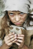 stock photo of heartbreak  - A portrait of a poor beggar child with a piece of bread in her hands - JPG