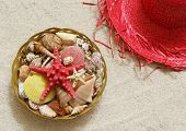 Seashells in the basket and straw hat on the sand