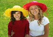 Mother and daughter outdoor, wearing hats