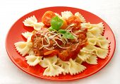 Farfalle with tomato sauce on red plate