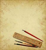 Vintage pens and wooden pen case on parchment background