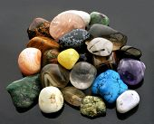 Collection of semi-precious gemstones, isolated on neutral grey background