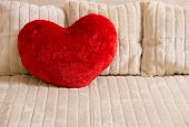 Fluffy soft red heart. Pillow on a bed.