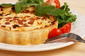 Quiche Lorene with Lettuce and tomatoes salad on a plate.