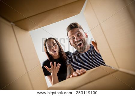 poster of The Surprised Man And Woman Unpacking, Opening Carton Box And Looking Inside. The Package, Delivery,