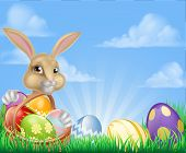 Easter Scene With Easter Bunny With A Basket Full Of Decorated Chocolate Easter Eggs In A Field poster