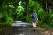 Woman with backpack walking on a wet road among green tropical trees