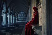 Mulher no manto vermelho rezando sozinho