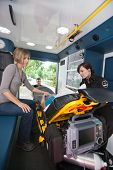 EMT professional caring for a senior woman in an ambulance, caregiver at side