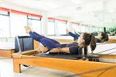 Full Length Of Determined Woman Pulling Resistance Bands On Pilates Reformer In Health Club poster