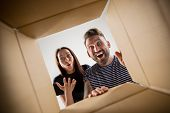 The Surprised Man And Woman Unpacking, Opening Carton Box And Looking Inside. The Package, Delivery, poster