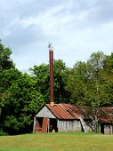 Old Barn Houses An Industrial Size Smoke Stack.  Stack Is Weathered And Rusting Along With Tin Roof  poster