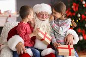 Little Children With Gift Boxes Sitting On Authentic Santa Claus Knees Indoors poster