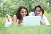 pic of computer-screen  - Couple lying on the grass looking at a laptop computer screen - JPG