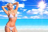 Sexy and fit blond woman bikini model relaxing by the sea