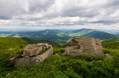 Two Boulders On The Grassy Hill. Mountain Range In The Distance. Overcast Sky In Summer poster