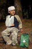 stock photo of sling bag  - First Aid treatment given to a young boy in the forest showing an arm sling and a head injury - JPG