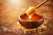 Honey dripping from honey dipper in wooden bowl.  Close-up. Healthy organic Thick honey dipping from poster