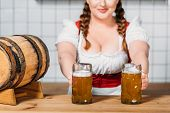 Oktoberfest Waitress In Traditional Bavarian Dress Putting Mugs Of Light Beer On Bar Counter With Be poster