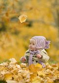 Baby In Autumn Leaves