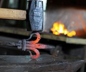 image of blacksmith shop  - Blacksmith forges a red - JPG