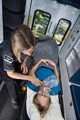 stock photo of triage  - Senior woman in ambulance receiving emergency medical care - JPG