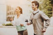 Young Happy Couple During Jogging In Morning. Healthcare And Active Lifestyle Concept. Morning Exerc poster