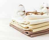 Multicolored Clean Towels With A Branch Of Cotton On A Light Wooden Background With Copy Space. Text poster