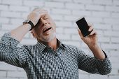 Old Man With Broken Mobile Phone Holding Head. Electronic Devices Concept. Mobile Device Hardware. M poster