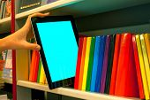 image of book-shelf  - Hand holding a tablet PC on the shelf - JPG