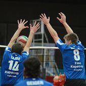 KAPOSVAR, HUNGARY - NOVEMBER 13: Roland Gergye (blue 8) in action at a Hungarian National Championship volleyball game Kaposvar (blue) vs. Nyiregyhaza (red), November 13, 2011 in Kaposvar, Hungary.