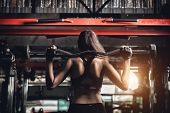Young Fitness Woman Execute Exercise With Exercise-machine In Gym poster