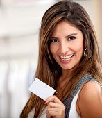 Happy woman holding a credit or debit card and smiling