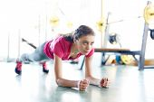 Young fit woman training in gym and doing plank exercise looking forward with determination poster