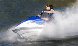 stock photo of waverunner  - action photo of young woman on seadoo at high speed - JPG