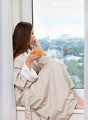 Woman drinking an orange juice.