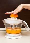 A Woman Squeezes Orange Juice In Kitchen