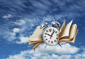 stock photo of time flies  - Old alarm clock flying with page wings time flies concept - JPG